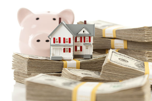 Toy House Surrounded by Money with Piggy Bank